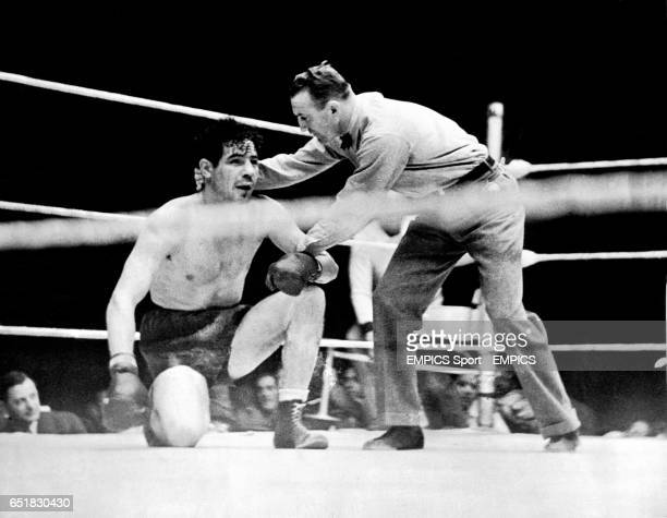 Referee Arthur Donovan right helps the defeated former Champion Max Baer left to his feet after Baer was knocked out in the fourth round by Joe Louis