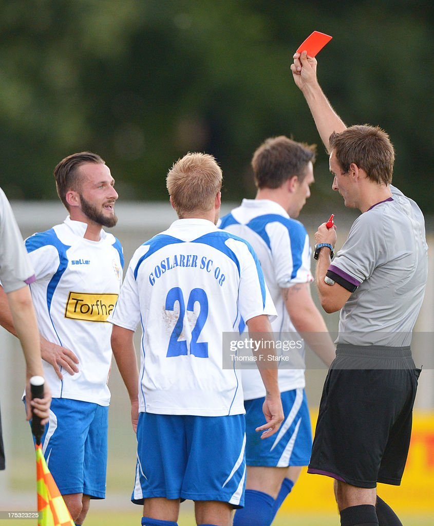 Referee Axel Martin (R) shows the red card to Tezcan Karabulut (L) of Goslar during the Regionalliga North match between BV Cloppenburg and Goslarer SC at stadium Cloppenburg on August 2, 2013 in Cloppenburg, Germany.