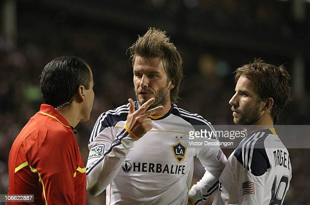 Referee Baldomero Toledo left and Mike Magee of the Los Angeles Galaxy looks on as David Beckham of the Los Angeles Galaxy pleads his case in the...