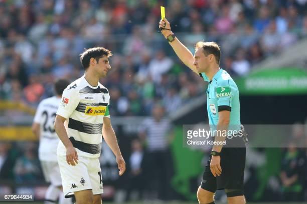 Referee Bastian Dankert shows Lars Stindl of Moenchengladbach the yellow card during the Bundesliga match between Borussia Moenchengladbach and FC...
