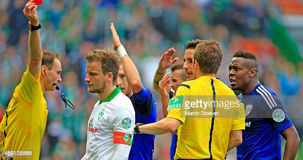 Referee Bastian Dankert shows Philipp Bargfrede of Bremen the red card during the Bundesliga match between Werder Bremen and FC Ingolstadt at...