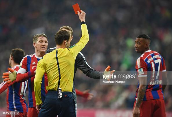 Referee Bastian Dankert shows the red card to Jerome Boateng of Muenchen during the Bundesliga match between FC Bayern Muenchen and FC Schalke 04 at...
