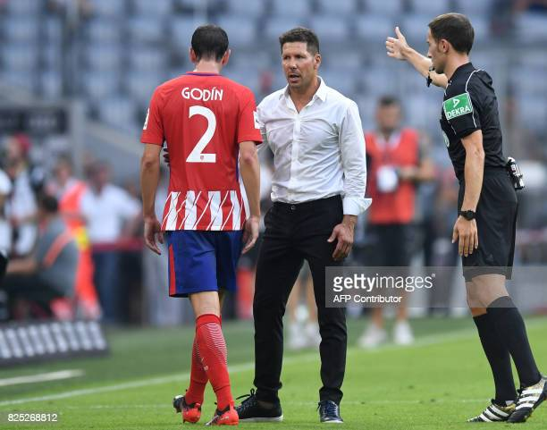 Referee Benjamin Brand gestures with Atletico Madrid's headcoach Diego Simeone and Atletico Madrid's Uruguayan Diego Godin as he gots the red card...