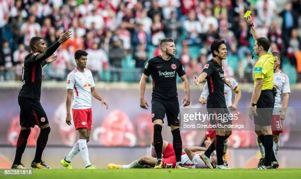 Referee Benjamin Brand shows a yellow card to Ante Rebic of Eintracht Frankfurt during the Bundesliga match between RB Leipzig and Eintracht...