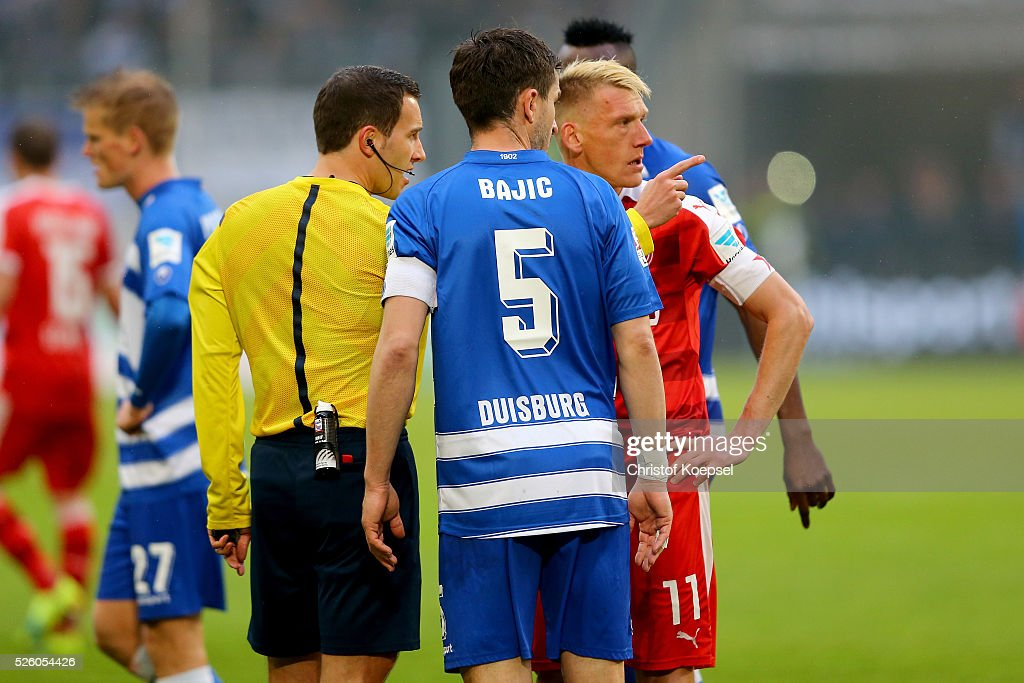 Referee Benjamin brand (L) stops the match after smokebombs and talks to Branimir Bajic (C) of Duisburg and <a gi-track='captionPersonalityLinkClicked' href=/galleries/search?phrase=Axel+Bellinghausen&family=editorial&specificpeople=634917 ng-click='$event.stopPropagation()'>Axel Bellinghausen</a> of Duesseldorf (R) during the 2. Bundesliga match between MSV Duisburg and Fortuna Duesseldorf at Schauinsland-Reisen-Arena on April 29, 2016 in Duisburg, Germany.