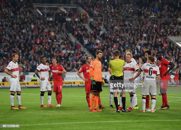 Referee Benjamin Cortus has a discussion with Andreas Beck of VfB Stuttgart and RonRobert Zieler of VfB Stuttgart before making a decision during the...