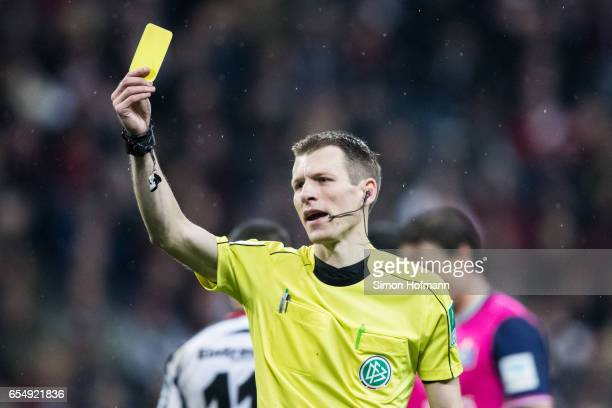 Referee Benjamin Cortus shows the yellow card during the Bundesliga match between Eintracht Frankfurt and Hamburger SV at CommerzbankArena on March...