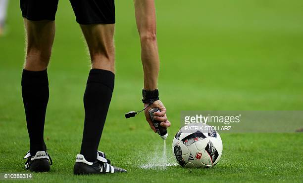 Referee Benjamin Cortus sprays marker on the freekick point during the German first division Bundesliga football match between 1 FC Cologne and RB...