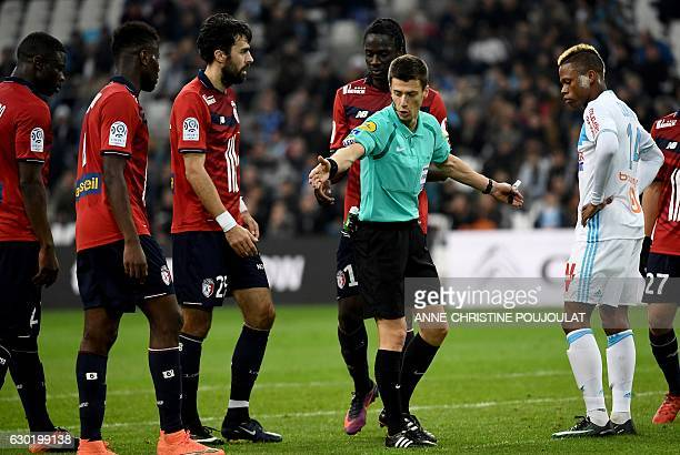 Referee Benoit Bastien gestures during the French L1 football match Marseille vs Lille on December 18 2016 at the Velodrome stadium in Marseille...