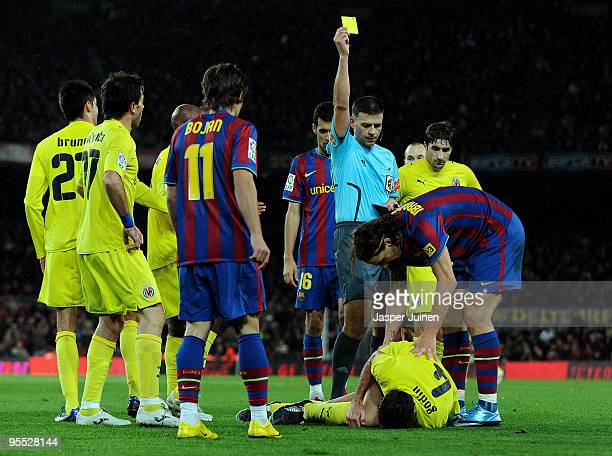 Referee Bernardino Vazquez shows Zlatan Ibrahimovic of FC Barcelona a yellow card for fouling Villarreal's Diego Godin who lies on the ground during...