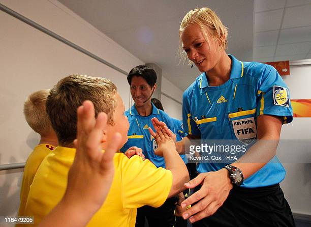 Referee Bibiana Steinhaus and her assistants slap hands with the kids prior to the FIFA Women's World Cup 2011 Group D match between Equatorial...