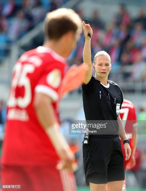 Referee Bibiana Steinhaus gestures next to Thomas Mueller of Muenchen during the DFB Cup first round match between Chemnitzer FC and FC Bayern...