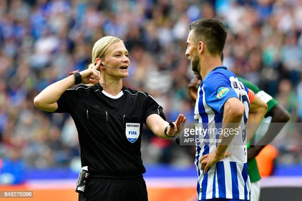 TOPSHOT Referee Bibiana Steinhaus talks with Berlin's Bosnian forward Vedad Ibisevic during German first division Bundesliga football match between...