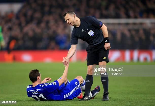 Referee Bjorn Kuipers helps up Chelsea's Nemanja Matic