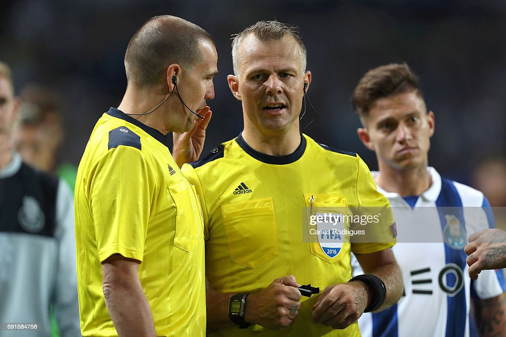 Referee Bjorn Kuipers talks to his assistant because a disallowed goal during the match between FC Porto v AS Rome UEFA Champions League playoff...