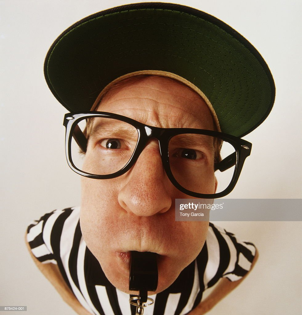 Referee blowing whistle, close-up, elevated view (wide angle) : Stock Photo