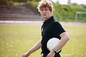Referee blowing whistle while carrying soccer ball on field