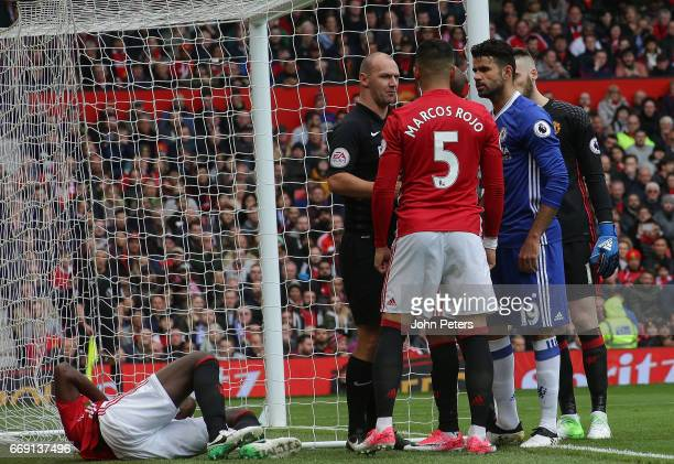 Referee Bobby Madley speaks to Marcos Rojo of Manchester United and Diego Costa of Chelsea while Eric Bailly lies injured during the Premier League...