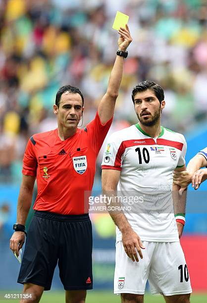 Referee Carlos Velasc Carballo of Spain shows Iran's forward Karim Ansari Fard the yellow card during a Group F football match between...