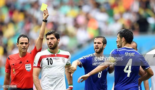 Referee Carlos Velasc Carballo of Spain shows Iran's forward Karim Ansari Fard the yellow card as BosniaHerzegovina's midfielder Miralem Pjanic and...