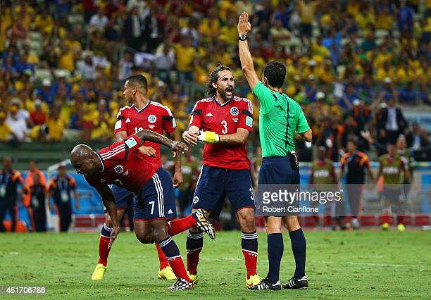 Referee Carlos Velasco Carballo gestures as Pablo Armero and Mario Yepes react during the 2014 FIFA World Cup Brazil Quarter Final match between...
