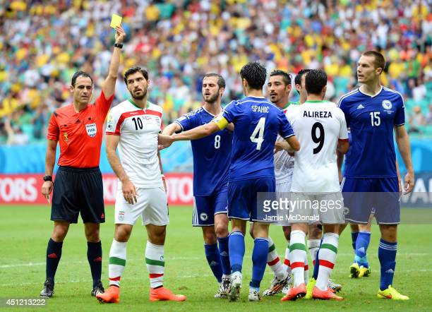 Referee Carlos Velasco Carballo shows a yellow card to Karim Ansari Fard of Iran during the 2014 FIFA World Cup Brazil Group F match between Bosnia...