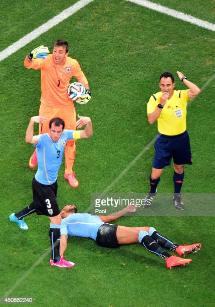 Referee Carlos Velasco Carballo signals for a trainer for Alvaro Pereira of Uruguay after a collision as teammates Diego Godin and Fernando Muslera...