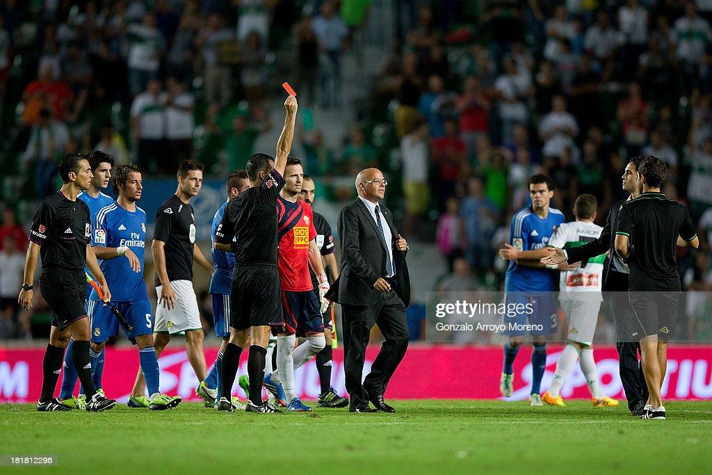 referee Cesar Muniz Fernandez shows the red card to Carlos Sanchez of Elche FC after the La Liga match between Elche FC and Real Madrid CF at Estadio Manuel Martinez Valero on September 25, 2013 in Elche, Spain.