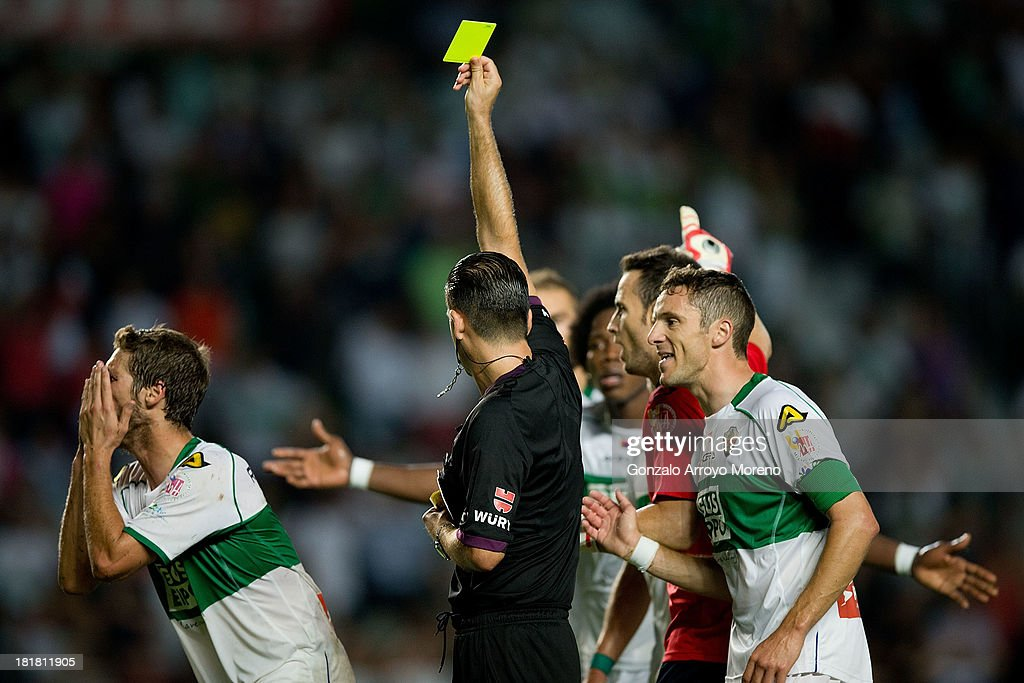 referee Cesar Muniz Fernandez shows the yellow card to Elche for a penalty to Real Madrid, that would be scored by Cristiano Ronaldo as second goal during the La Liga match between Elche FC and Real Madrid CF at Estadio Manuel Martinez Valero on September 25, 2013 in Elche, Spain.