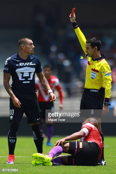 Referee Cesar Ramos shows a red card to Nicolas Castillo of Pumas after a foul over Egidio ArŽevalo of Veracruz during the 15th round match between...