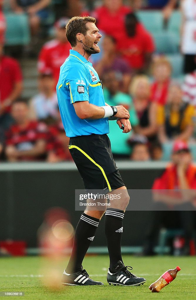 Referee, Chris Beath avoids bottles being thrown by supporters during the round 15 A-League match between the Western Sydney Wanderers and the Central Coast Mariners at Parramatta Stadium on January 6, 2013 in Sydney, Australia.