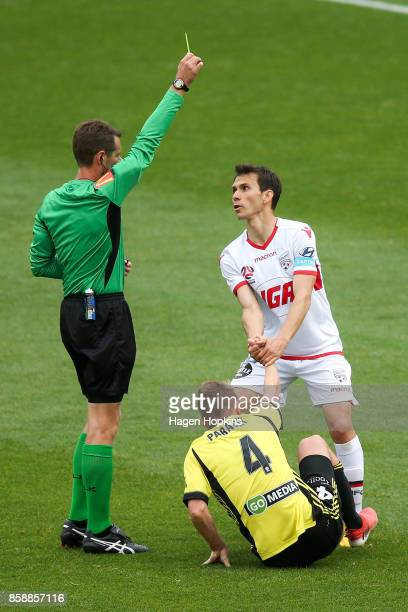 Referee Chris Beath shows Isaias of Adelaide United a yellow card after fouling Goran Paracki of the Phoenix during the round one ALeague match...