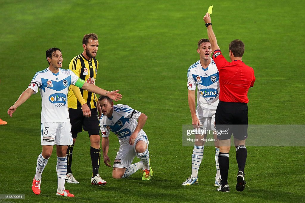Referee Chris Beath shows Nick Ansell of the Victory a yellow card during the round 27 A-League match between Wellington Phoenix and Melbourne Victory at Westpac Stadium on April 12, 2014 in Wellington, New Zealand.