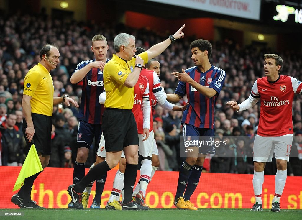 """Referee Chris Foy awards the goal to Arsenal after a discussion with the players during the English Premier League football match between Arsenal and Stoke City at the Emirates Stadium in North London, England on Febuary 2, 2013. Arsenal won 1-0. AFP PHOTO/Olly GREENWOOD USE. No use with unauthorized audio, video, data, fixture lists, club/league logos or """"live"""" services. Online in-match use limited to 45 images, no video emulation. No use in betting, games or single club/league/player publications."""