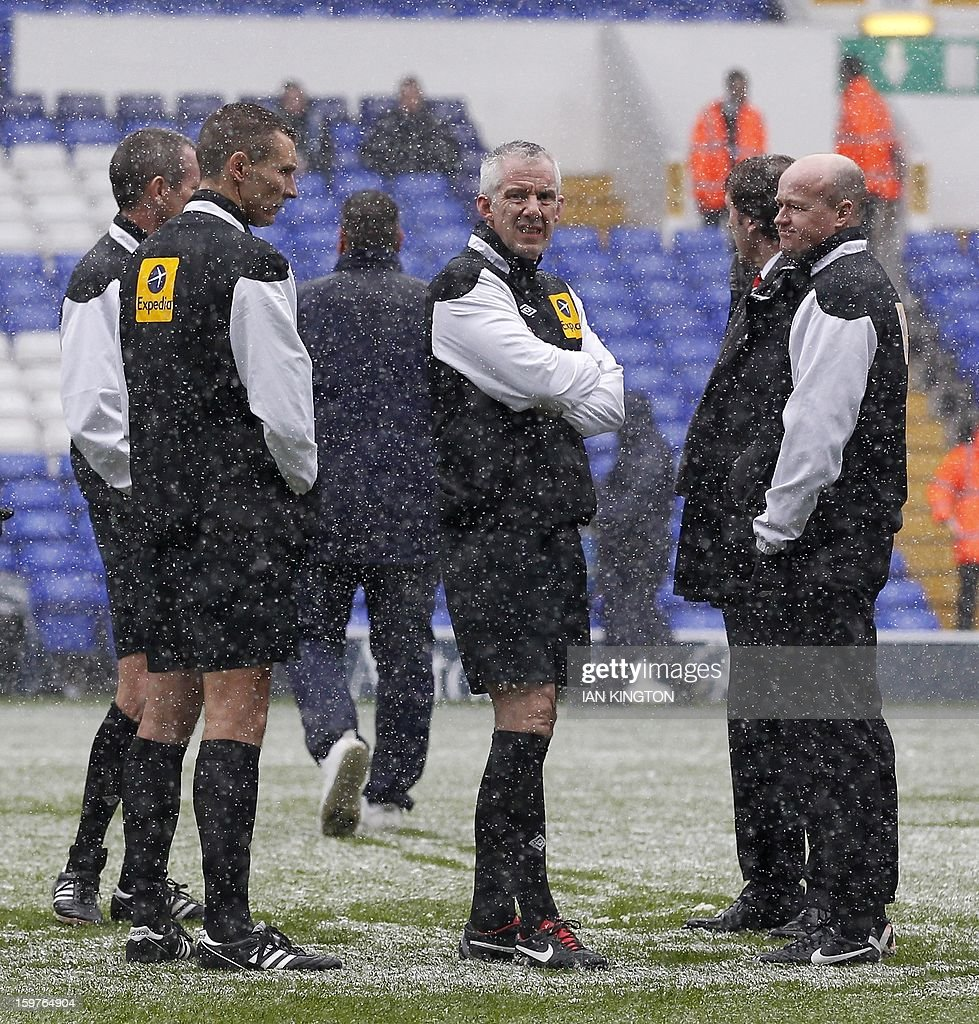 "Referee Chris Foy (c) holds a pitch inspection before kick off for an English Premier League football match between Tottenham Hotspur and Manchester United at White Hart Lane in London, England, on January 20, 2013. AFP PHOTO/Ian KINGTON - RESTRICTED TO EDITORIAL USE. No use with unauthorized audio, video, data, fixture lists, club/league logos or ""live"" services. Online in-match use limited to 45 images, no video emulation. No use in betting, games or single club/league/player publications."