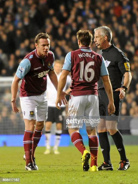Referee Chris Foy is on hand as Kevin Nolan and Mark Noble of West Ham square up during the Barclays Premier League match between Fulham and West Ham...
