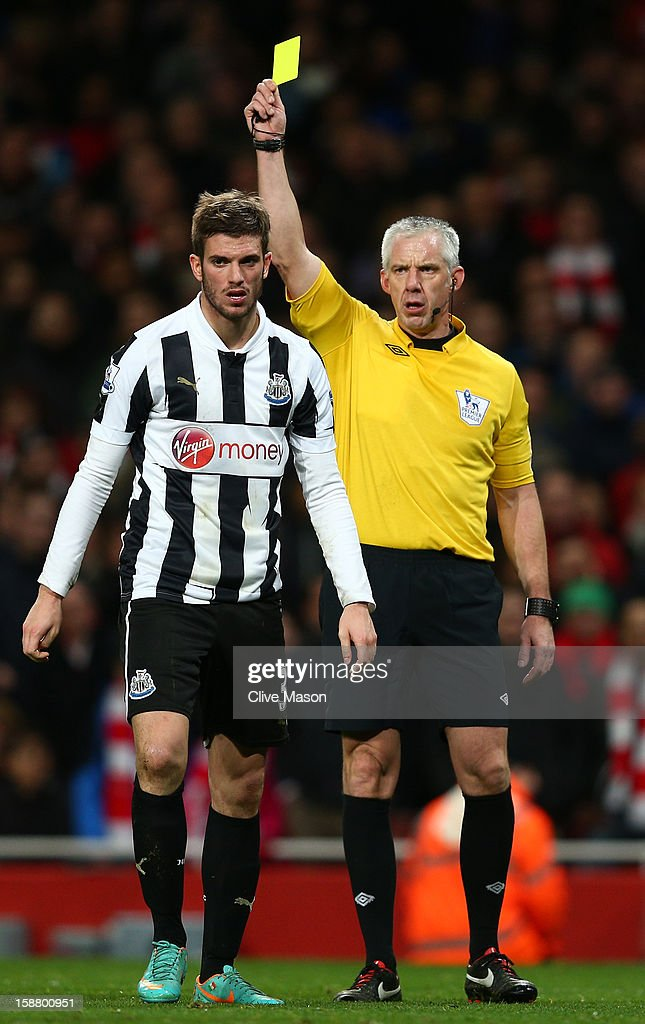 Referee Chris Foy shows Davide Santon of Newcastle United a yellow card during the Barclays Premier League match between Arsenal and Newcastle United at the Emirates Stadium on December 29, 2012 in London, England.