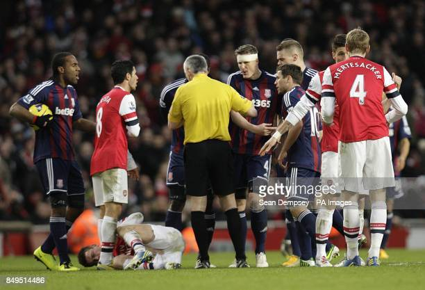 Referee Chris Foy shows Stoke City's Ryan Shawcross a yellow card for a foul on Arsenal's Laurent Koscielny