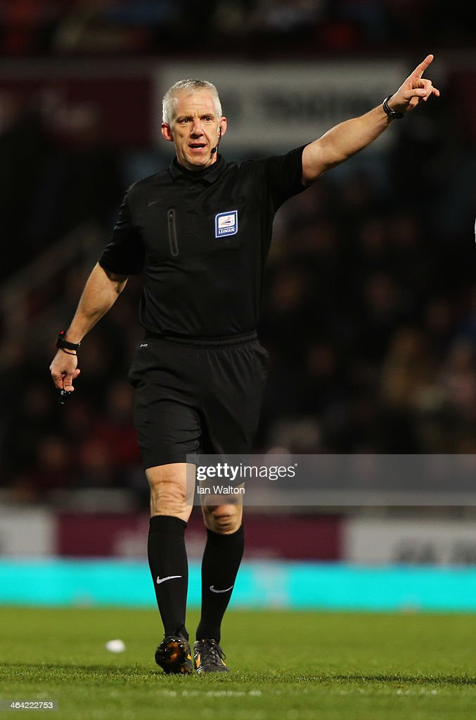 Referee Chris Foy signals during the Capital One Cup Semi-Final, Second Leg match between West Ham United and Manchester City at Boleyn Ground on January 21, 2014 in London, England.