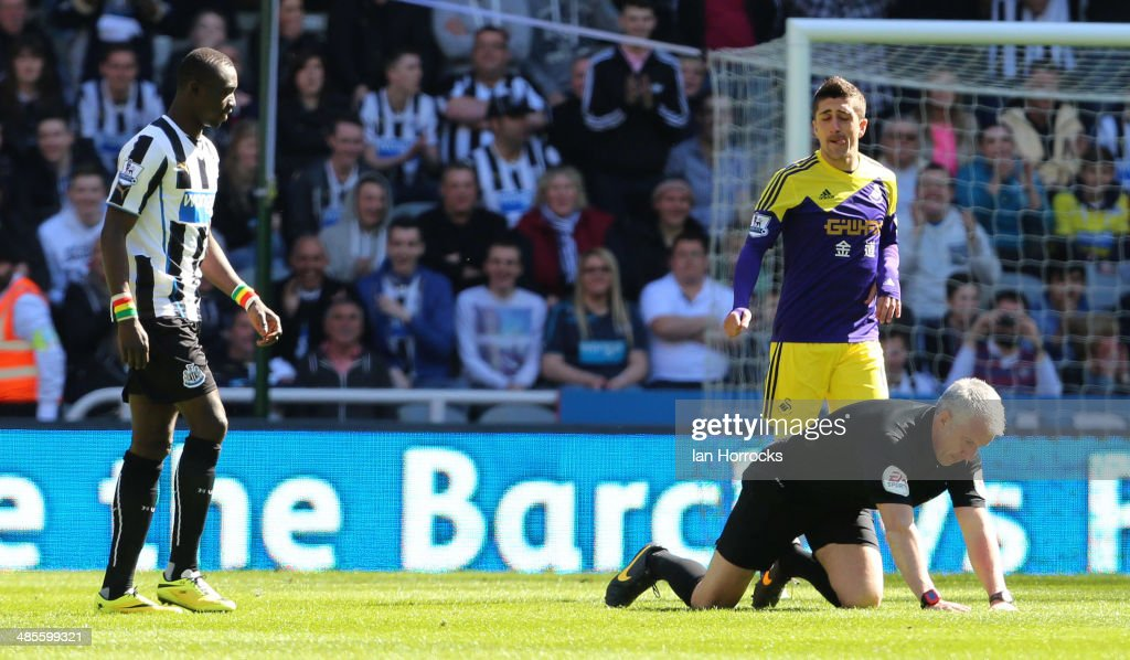 Referee Chris Foy struggles to his feet after the official was hit in the face by the ball during the Barclays Premier League match between Newcastle United and Swansea City at St James' Park on April 19, 2014 in Newcastle upon Tyne, England.