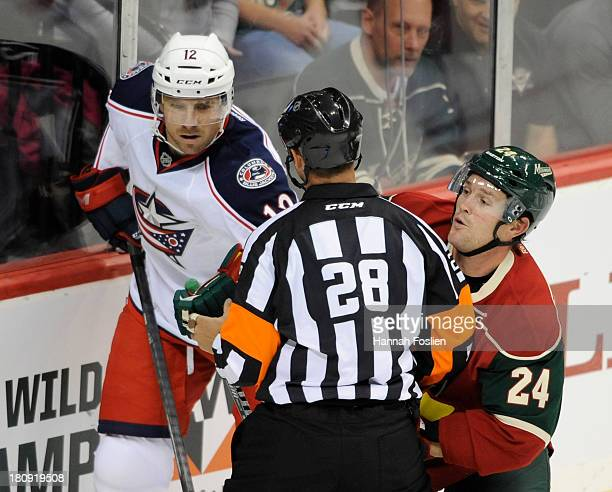 Referee Chris Lee blocks the path of Ryan Craig of the Columbus Blue Jackets and Matt Cooke of the Minnesota Wild after Lee tripped on the ice during...