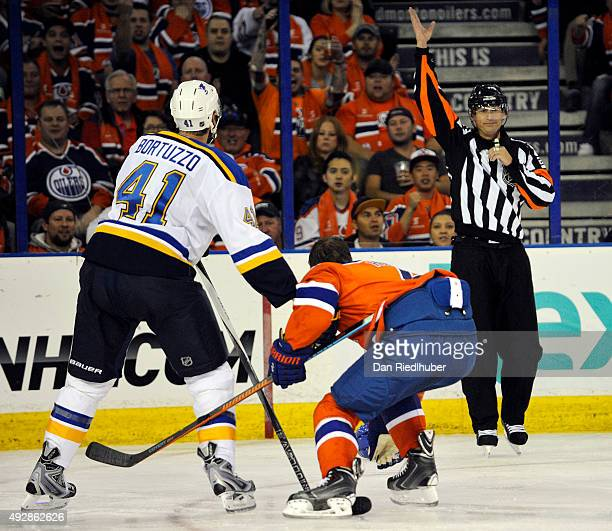 Referee Chris Lee calls a penalty against Robert Bortuzzo of the St Louis Blues as he knocks the helmet off Taylor Hall of the Edmonton Oilers at...