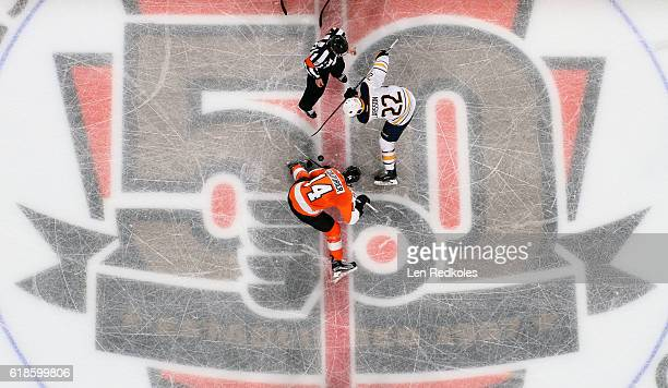 Referee Chris Lee drops the puck on a faceoff between Sean Couturier of the Philadelphia Flyers and Johan Larsson of the Buffalo Sabres on October 25...