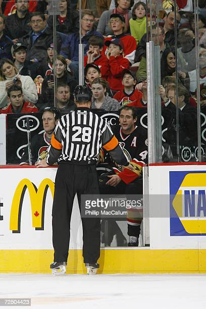 Referee Chris Lee has a discussion at the penalty box with Chris Phillips of the Ottawa Senators as Joe Corvo looks on during the NHL game against...
