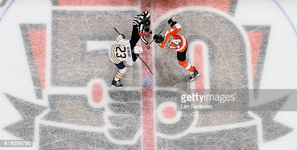 Referee Chris Lee prepares to drop the puck on a faceoff between Sean Couturier of the Philadelphia Flyers and Sam Reinhart of the Buffalo Sabres on...
