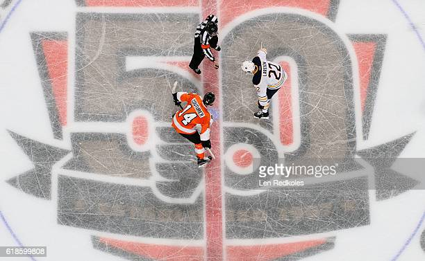 Referee Chris Lee prepares to drop the puck on a faceoff between Sean Couturier of the Philadelphia Flyers and Johan Larsson of the Buffalo Sabres on...