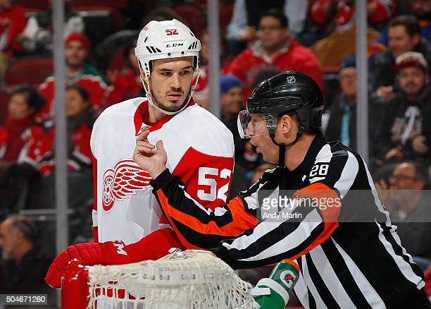 Referee Chris Lee talks with Jonathan Ericsson of the Detroit Red Wings during the game against the New Jersey Devils at the Prudential Center on...