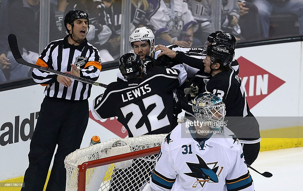 NHL referee Chris Rooney #5 and linesman Steve Miller #89 try to break up the scrum between James Sheppard #15 of the San Jose Sharks and Trevor Lewis #22 and Tyler Toffoli #73 of the Los Angeles Kings during the first period of Game Three of the First Round of the 2014 NHL Stanley Cup Playoffs at Staples Center on April 22, 2014 in Los Angeles, California.