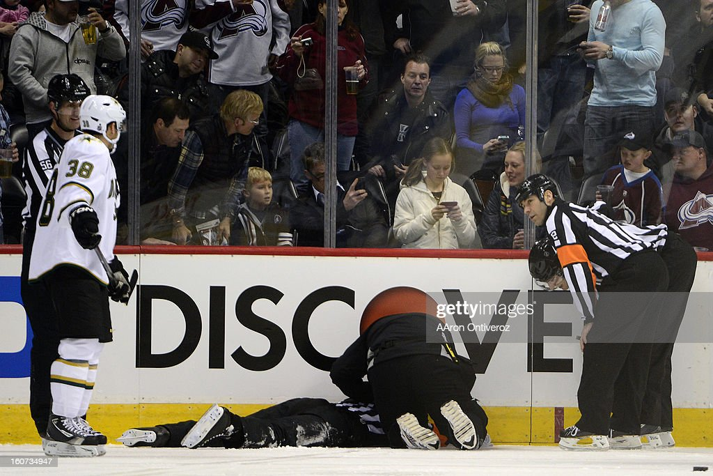 Referee Chris Rooney lies on the ice after being struck by a puck during the first period of action. Colorado Avalanche versus the Dallas Stars at the Pepsi Center on February 4, 2012.