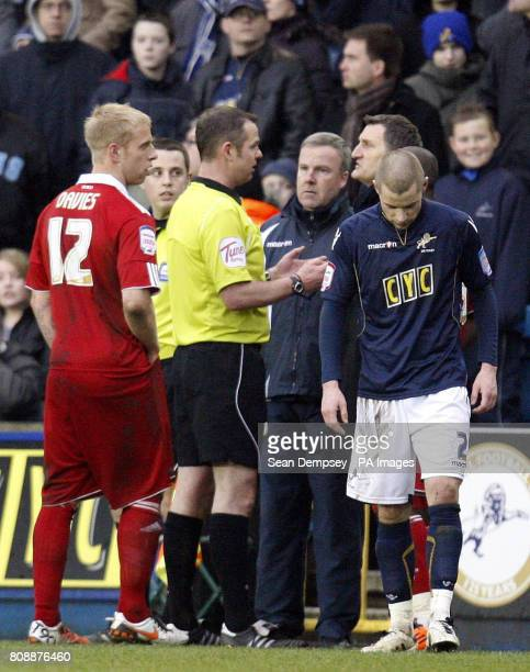 Referee Chris Sarginson talks to Kenny Jackett and Tony Mowbray about possibley stopping the game after a lines man had some trouble with the fans...
